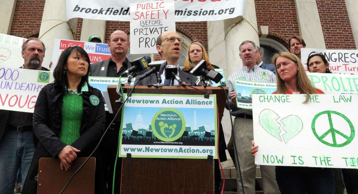 Members of Newtown Action Alliance including Po Murray left and Monte Frank at podium, both of Newtown, and gun control supporters met on the steps of Newtown's Edmond Town Hall in Newtown. They were part of a national action to read names of shooting victims since 12/14/12, coinciding with a threat of filibuster in Washington. Mara Lavitt/New Haven Register4/10/13