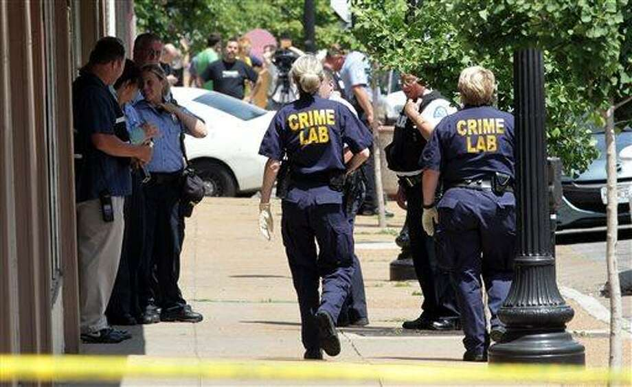 St. Louis police work the scene where four people were found dead in a business along Cherokee Street south of downtown in St. Louis, on Thursday, June 13, 2013. The St. Louis Police Department posted on its official Twitter account that two women and two men are dead. (AP Photo/St. Louis Post-Dispatch, Robert Cohen) EDWARDSVILLE INTELLIGENCER OUT; THE ALTON TELEGRAPH OUT Photo: AP / St. Louis Post-Dispatch