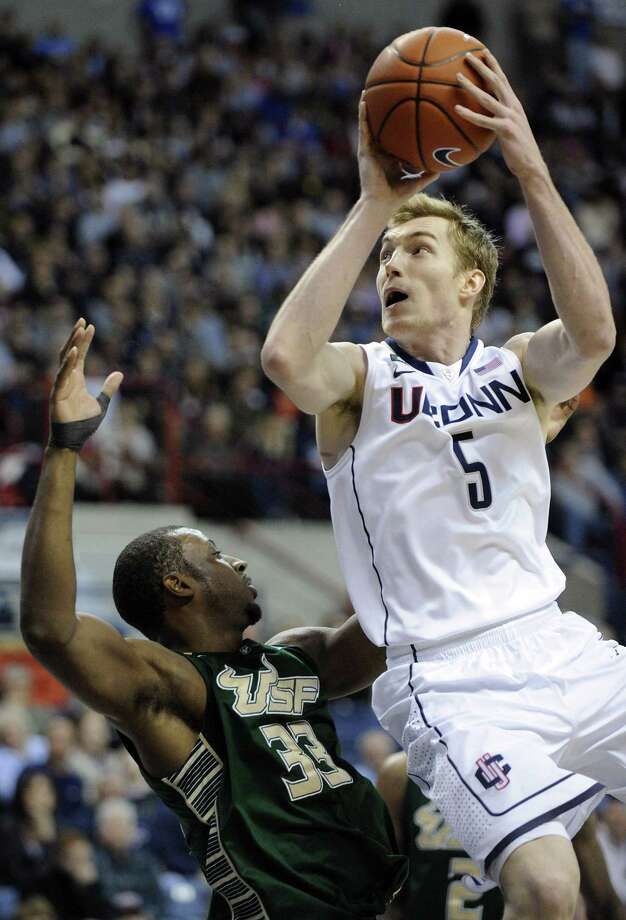 Connecticut's Niels Giffey (5) drives past South Florida's Kore White during the second half of an NCAA college basketball game in Storrs, Conn., Sunday, Feb. 3, 2013. Connecticut won the game in overtime 69-64. (AP Photo/Fred Beckham) Photo: ASSOCIATED PRESS / AP2013