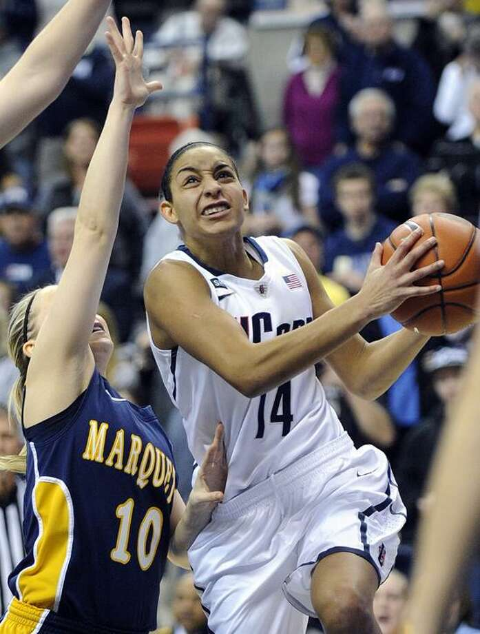 Connecticut's Bria Hartley, right, drives past Marquette's Brooklyn Pumroy during the first half of an NCAA college basketball game in Storrs, Conn., Tuesday, Feb. 5, 2013. (AP Photo/Fred Beckham) Photo: AP / AP2013