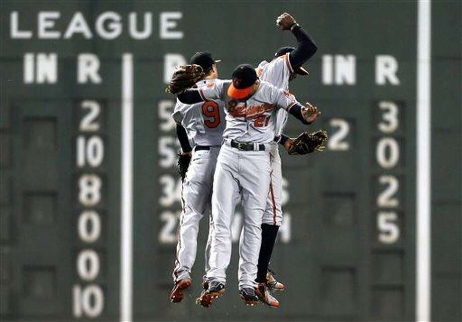 Baltimore Orioles' Nate McLouth, Nick Markakis and Adam Jones, from left, celebrate the Orioles' 8-5 win against the Boston Red Sox in a baseball game in Boston, Wednesday, April 10, 2013. (AP Photo/Michael Dwyer) Photo: AP / AP