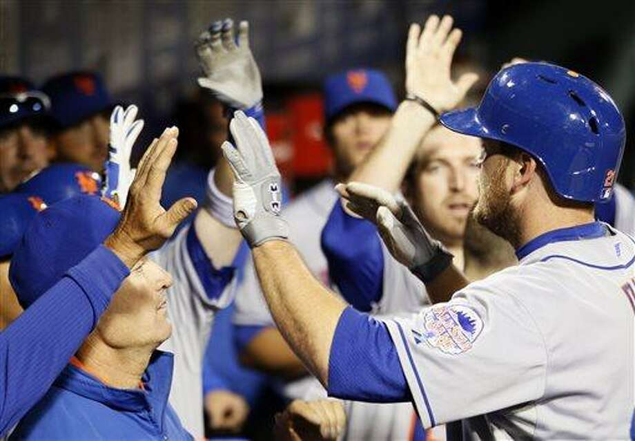 New York Mets' Lucas Duda returns to high-fives in the dugout after hitting a home run during the fourth inning of a baseball game against the Philadelphia Phillies on Wednesday, April 10, 2013, in Philadelphia. (AP Photo/Tom Mihalek) Photo: AP / FR148949 AP