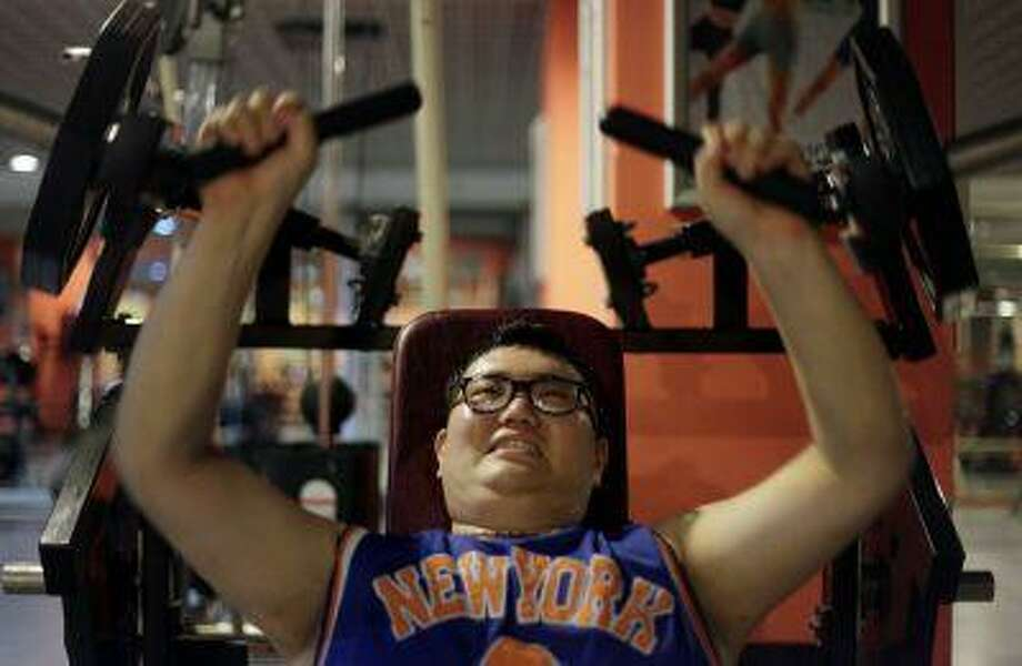 A man lifts weight as part of his fitness training at a weight loss campus. Photo: REUTERS / X80006