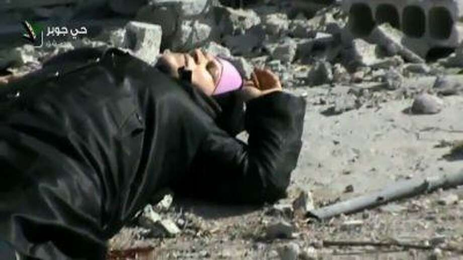 This image taken from video obtained from Shaam News Network, which has been authenticated based on its contents and other AP reporting, shows an injured Syrian woman lying in a street before her rescue by rebels from a firefight in the Jobar neighborhood in Damascus, Syria, April 10. Photo: AP / Shaam News Network