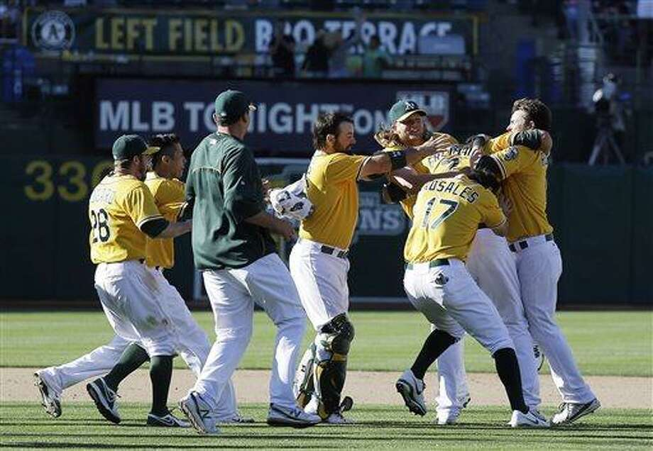 Oakland Athletics' Nate Freiman, second from right, is mobbed by his teammates after hitting the game-winning RBI single off New York Yankees pitcher Mariano Rivera in the 18th inning of a baseball game Thursday, June 13, 2013, in Oakland, Calif. Oakland won 3-2 in 18 innings. (AP Photo/Eric Risberg) Photo: AP / AP
