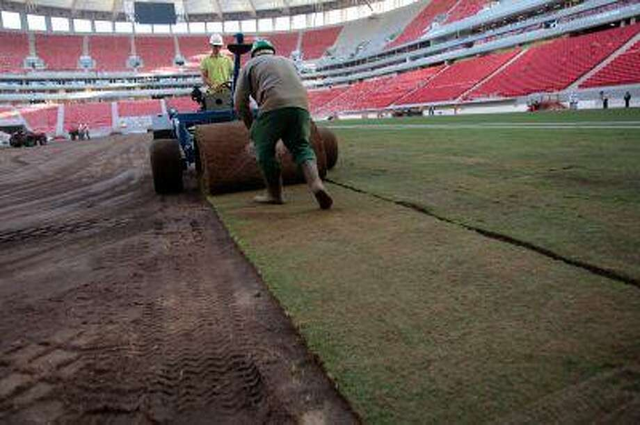 FILE - In this April 29, 2013 file photo, employees rollout lawn turf at the National Stadium during reconstruction of the stadium in Brasilia, Brazil. No matter how well Brazil does hosting the Confederations Cup, it will be hard to say the country succeeded in its preparations. There were delays and cost overruns in stadiums across the country, few infrastructure projects were completed and the nation's capacity to host the tournament was put in doubt several times. Photo: AP / AP