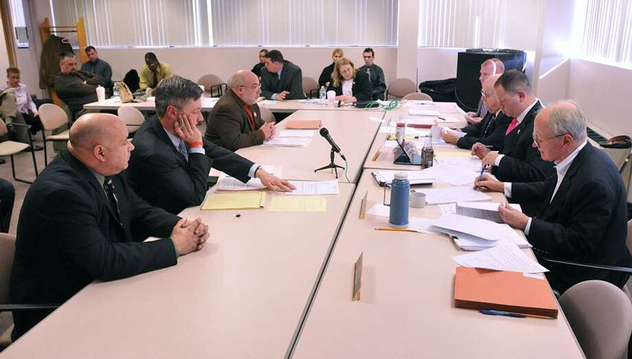 Middletown--Michael Polito, left, of New Fairfield appears before the Board of Firearms Permit Examiners with his attorney, Ralph Sherman (2nd from left). Testifying for the town of New Fairfield is first selectman John Hodge (3rd from left). Polito was appealing a pistol permit denial from his town.   Photo-Peter Casolino 1/24/13