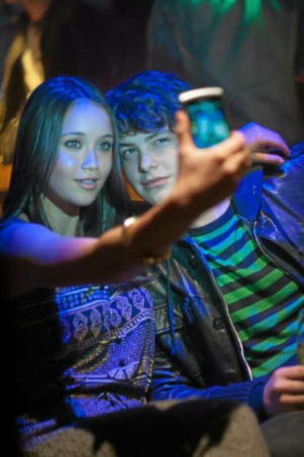"""Katie Chang and Israel Broussard smile for the (cell-phone) camera in a nightclub scene in """"The Bling Ring"""""""