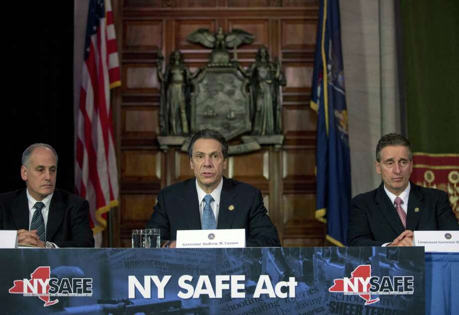 New York Gov. Andrew Cuomo, center, speaks during a news conference announcing an agreement with legislative leaders on New York's Secure Ammunition and Firearms Enforcement Act in the Red Room at the Capitol on Monday, Jan. 14, 2013, in Albany, N.Y. Also pictured are Secretary to the Governor Larry Schwartz, left, and Lt. Gov. Robert Duffy. (AP Photo/Mike Groll) Photo: ASSOCIATED PRESS / AP2013