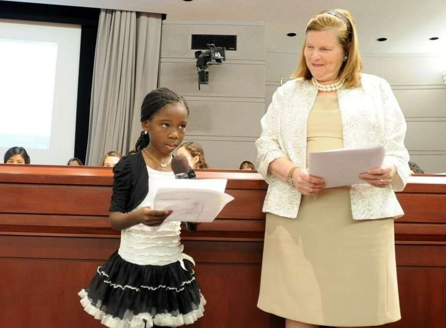 "Celine Assahoua, of West Haven, 6, and a first grader at Washington School in West Haven, reads her short essay on her mother, whom she calls a hero, left,  as Elaine Zimmerman, Executive Director of the Connecticut Commission on Children, right, listens during the Connecticut Commission on Children sponsored program ""Celebrating Community, Safety and Bravery: An Artistic Student Tribute to Newtown and Connecticut""  Wednesday, June 5, 2013 at the Legislative Office Building in Hartford, Connecticut where over 70 student artists and writers off all grades were present to show off their work.  ""The event honors the resilience of Newtown, the strength of community, and the healing power of art,"" according to a press release.  Photo by Peter Hvizdak / New Haven Register Photo: New Haven Register / ©Peter Hvizdak /  New Haven Register"