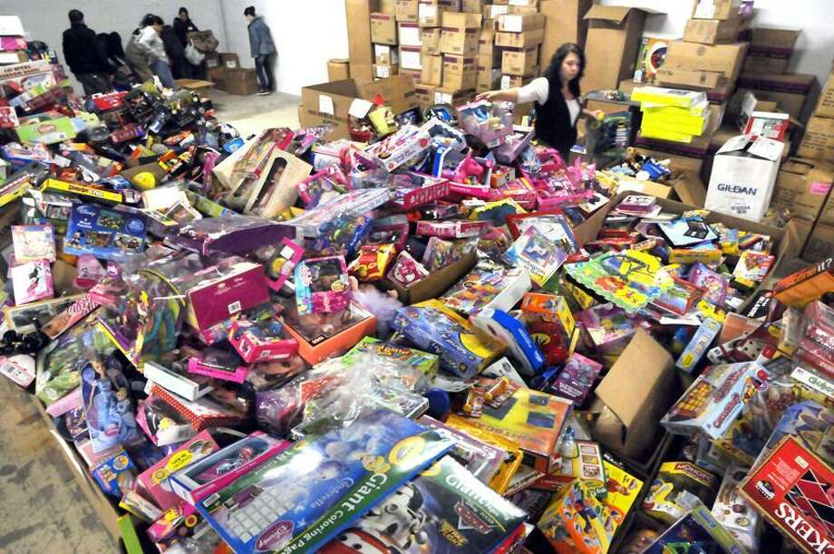 Thousands of toys, stuffed animals, school supplies, cards and letters are pouring into Newtown after the shooting tragedy. Volunteer Lisa Ferrucci of Waterbury, a school paraprofessional, helps sort toys at the Simm Lane location. Mara Lavitt/New Haven Register 12/28/12