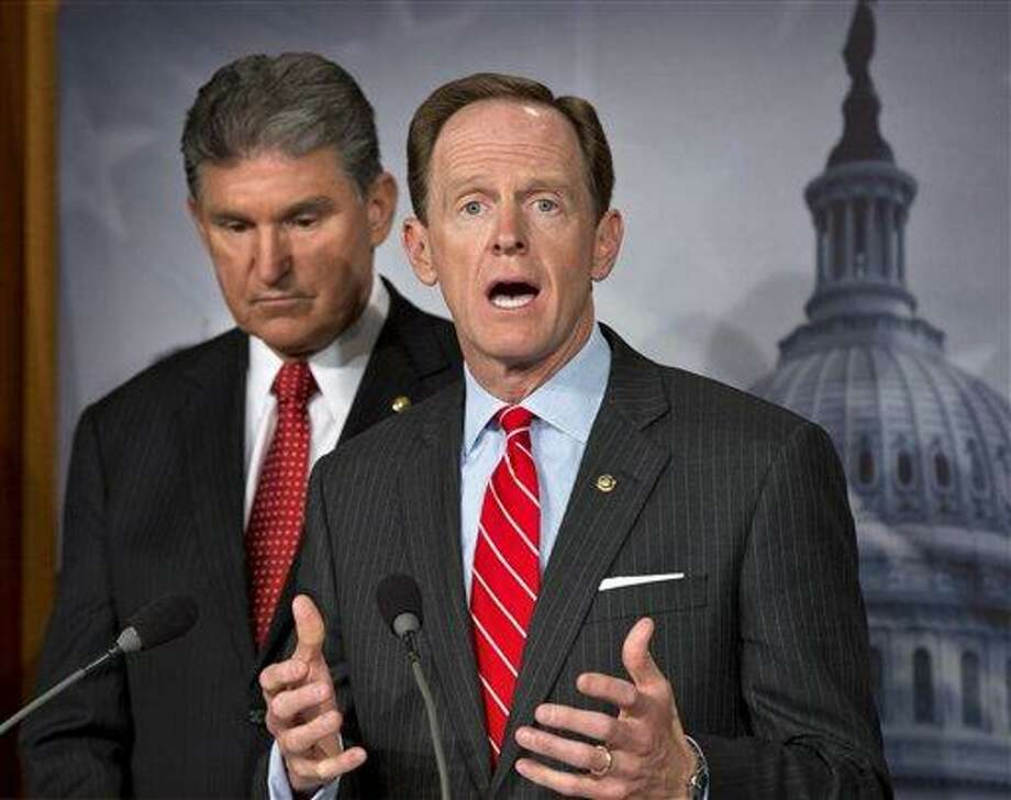 """Sen. Joe Manchin, <a href=""""http://D-W.Va"""">D-W.Va</a>. listens at left, as Sen. Patrick Toomey, R-Pa. announce that they have reached a bipartisan deal on expanding background checks to more gun buyers, Wednesday, April 10, 2013, on Capitol Hill in Washington.  (AP Photo/J. Scott Applewhite) Photo: ASSOCIATED PRESS / AP2013"""