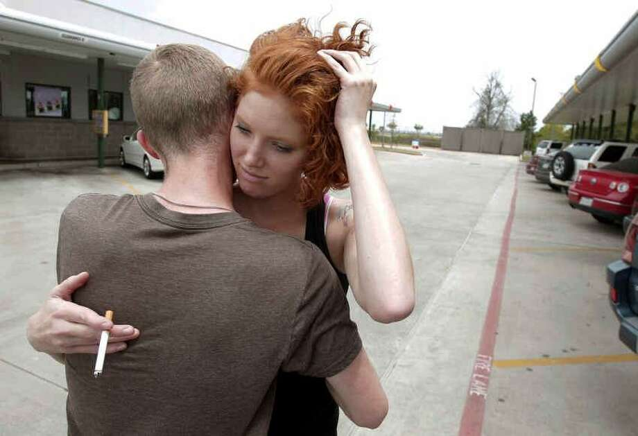 Cassie Foe hugs classmate Christian Wilson after leaving from the Cy-Fair campus of Lone Star Community College in Cypress, Texas, where she witnessed a man getting stabbed Tuesday, April 9, 2013. A student went on a building-to-building stabbing attack at the community college Tuesday, wounding at least 14 people before being subdued and arrested, authorities said. (AP Photo/Houston Chronicle, Melissa Phillip)  MANDATORY CREDIT Photo: ASSOCIATED PRESS / AP2013