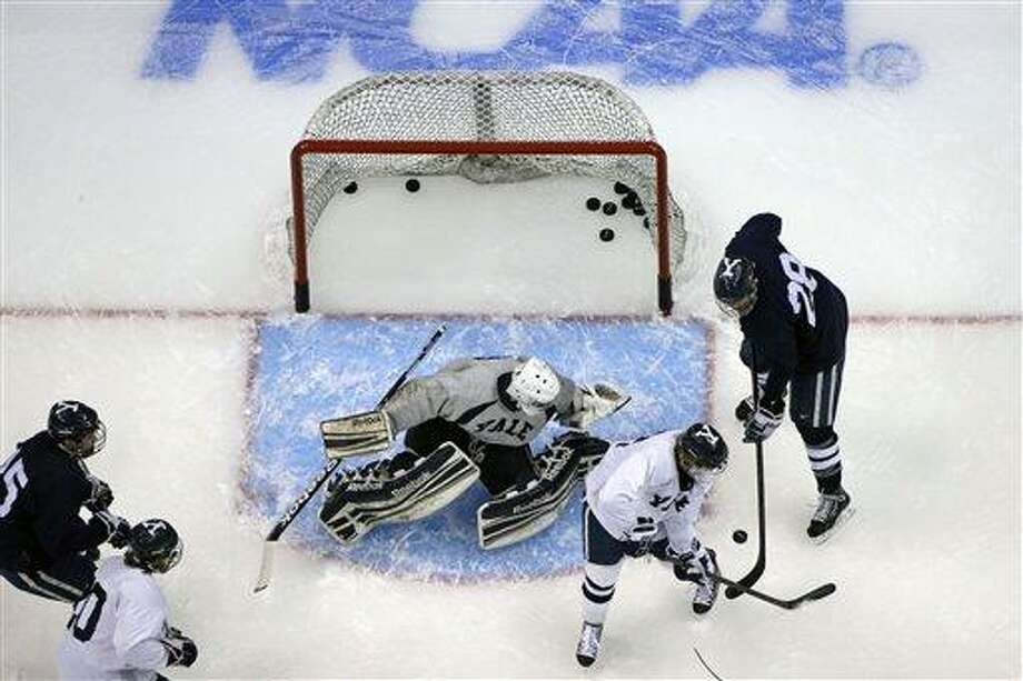 Yale goalie Connor Wilson looks to stop a shot by Yale forward Antoine Laganiere (28) during an NCAA college hockey practice at the Consol Energy Center in Pittsburgh, Wednesday, April 10, 2013. (AP Photo/Gene J. Puskar) Photo: ASSOCIATED PRESS / AP2013