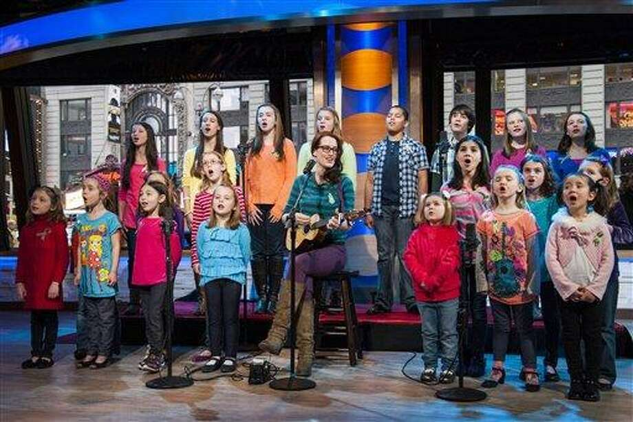 """Ingrid Michaelson accompanied by children from Newtown, Conn. and Sandy Hook Elementary school perform """"Somewhere Over the Rainbow"""" on ABC's """"Good Morning America"""" on Tuesday, Jan. 15, 2013 in New York.  The Children who survived last month's shooting rampage, recorded a version of """"Over the Rainbow"""" to raise money for charity.  They recorded the song at the home of two former members of the Talking Heads rock band. It went on sale Tuesday on Amazon and iTunes, with proceeds benefiting a local United Way and the Newtown Youth Academy. (Photo by Charles Sykes/Invision/AP) Photo: Charles Sykes/Invision/AP / AP2013"""