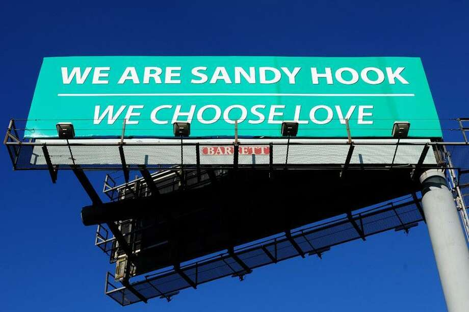 """A Barrett Outdoor Communications billboard reading """"WE ARE SANDY HOOK/WE CHOOSE LOVE"""" is photographed by exit 42 of I-95 in West Haven. Photo by Arnold Gold/New Haven Register"""