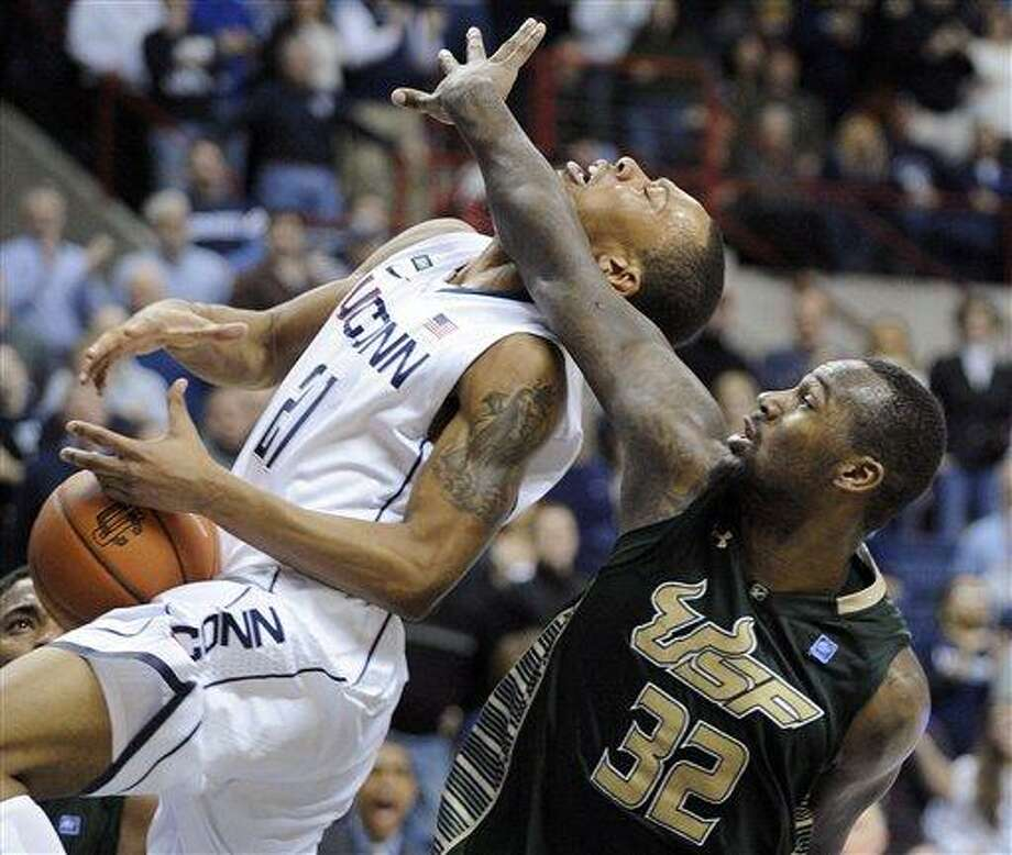 Connecticut's Omar Calhoun, left, is fouled by South Florida's Toarlyn Fitzpatrick during the second half of an NCAA college basketball game in Storrs, Conn., Sunday, Feb. 3, 2013. Connecticut won the game in overtime 69-64. (AP Photo/Fred Beckham) Photo: AP / FR153656 AP