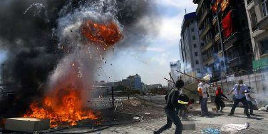 Protesters react after an explosion on a barricade during clashes in Istanbul's Taksim square June 11.