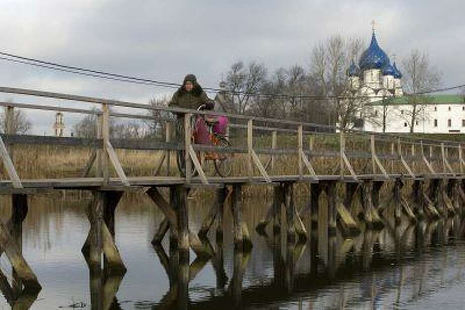 A pensioner wheels her bicycle across a wooden bridge on the Kamenka river in Suzdal; in the background, the Cathedral of the Nativity of the Virgin, one of Suzdal's oldest churches, was built in 1222 and rebuilt in 1528. (Bloomberg News/Andrey Rudakov)