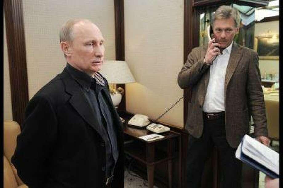 Russia's Prime Minister Vladimir Putin and his spokesman Dmitry Peskov.