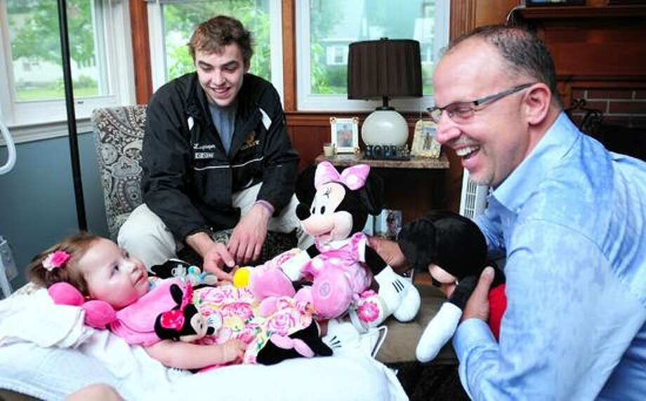 Arnold Gold -- RegisterEva Grace Kelly (left) meets Frank Squeo (right), founder and president of Baking Memories 4 Kids, at her home in West Haven on 6/11/2013.  Squeo presented Eva Grace and her family and nurses with an all expenses paid trip to Disneyworld.   In back is her cousin, Sean Langrieger.