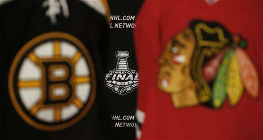 The 2013 NHL Stanley Cup log is seen between the sweaters of the Boston Bruins and Chicago Blackhawks during a news conference for the Stanley Cup Final hockey series between the Blackhawks and the Bruins Tuesday, June 11, 2013 in Chicago. The first game of the Stanley Cup final series is Wednesday in Chicago.(AP Photo/Charles Rex Arbogast) Photo: AP / AP