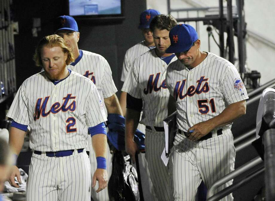 New York Mets' Justin Turner (2), batting coach Dave Hudgens (51) and teammates leave the dugout after they lost to the St. Louis Cardinals 9-2 in a baseball game at Citi Field on Tuesday, June 11, 2013 in New York. (AP Photo/Kathy Kmonicek) Photo: ASSOCIATED PRESS / AP2013