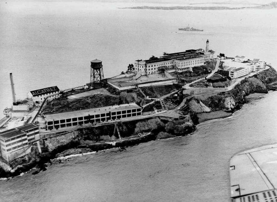 """This is an undated aerial view of the federal prison island Alcatraz, also known as """"The Rock,"""" in the San Francisco Bay, California. On the left are the facilities of the Model Industries buildings, up on the hill is the cellhouse with the high-walled recreation yard in front. (AP Photo) Photo: ASSOCIATED PRESS"""