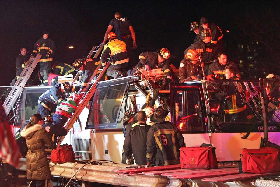 Emergency personnel remove passengers at the scene of a bus crash Saturday in Boston. Authorities say a charter bus heading from Harvard University to Pennsylvania has struck a bridge in Boston, injuring 33 people. AP Photo/The Boston Herald, Stuart Cahill Photo: ASSOCIATED PRESS / AP2013