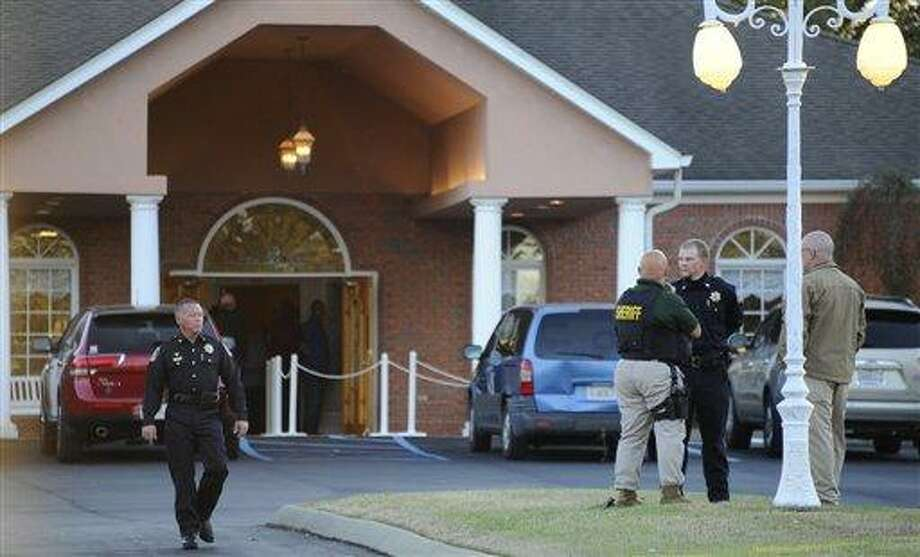 """Law enforcement personnel wait outside the funeral home as people pay their respects to Charles Albert """"Chuck"""" Poland, the 66 year old bus driver who gave his life to save the children on his bus, Saturday, in Slocumb, Ala. As the police standoff with an Alabama man accused of holding a 5-year-old boy hostage continued Saturday, a nearby community prepared to bury, Poland, the beloved bus driver who was shot to death trying to protect children on his bus when the episode began days earlier AP Photo/AL.com, Joe Songer Photo: AP / AL.COM"""