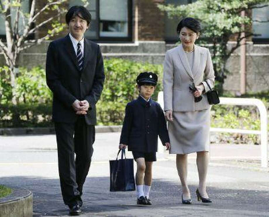 Prince Hisahito, center, accompanied by his parents Prince Akishino, left, and Princess Kiko, arrive at Ochanomizu University Elementary School for his entrance ceremony in Tokyo on April 7. Photo: AFP/Getty Images / 2013 AFP