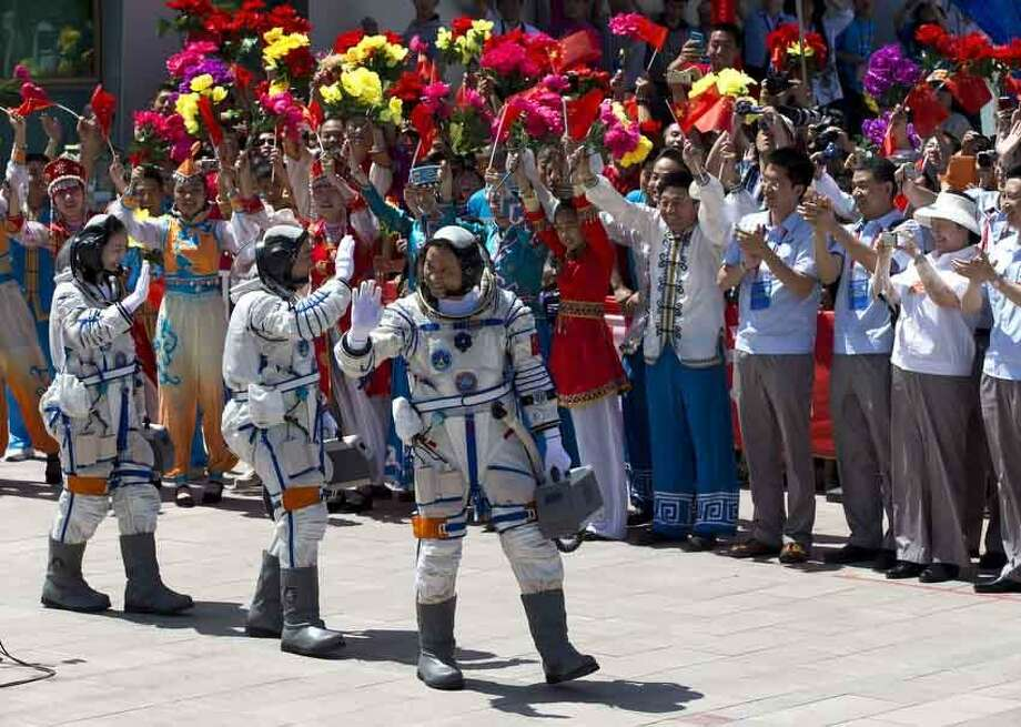China's astronauts from left, Wang Yaping, Zhang Xiaoguang and Nie Haisheng wave as they leave the Jiuquan satellite launch center for the launch site near Jiuquan in western China's Gansu province, Tuesday, June 11, 2013. Three Chinese astronauts will take flight on Tuesday evening if weather permits, aboard the spacecraft to the dock with China's Tiangong 1 space lab. (AP Photo/Andy Wong) Photo: ASSOCIATED PRESS / AP2013