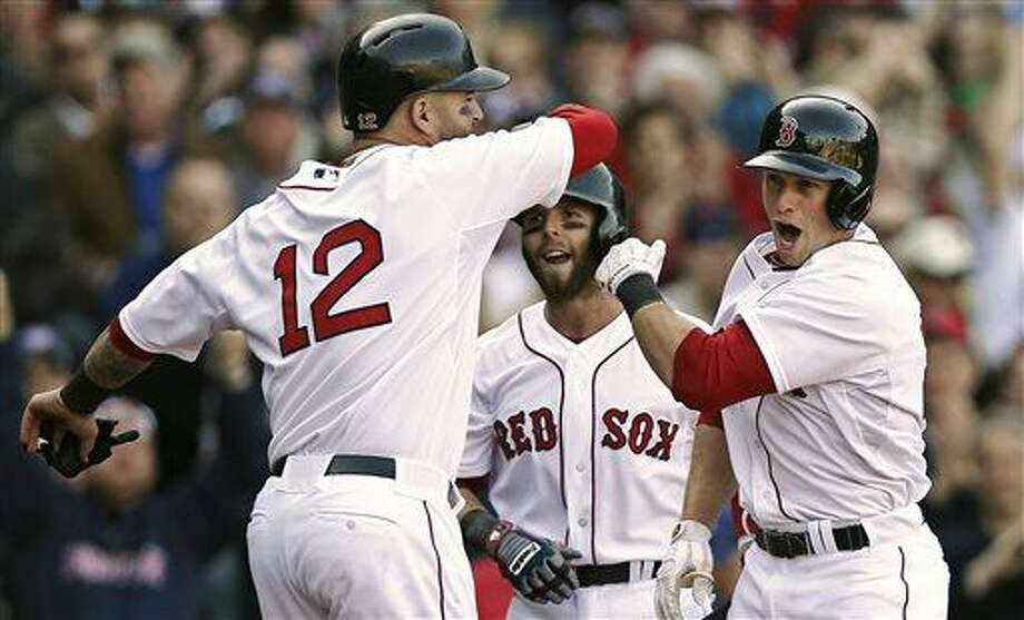 Boston Red Sox's Daniel Nava, right, is greeted by Dustin Pedroia and Mike Napoli (12) after hitting a three-run home run during the seventh inning of a baseball game against the Baltimore Orioles at Fenway Park in Boston, Monday, April 8, 2013. (AP Photo/Winslow Townson) Photo: AP / FR170221 AP