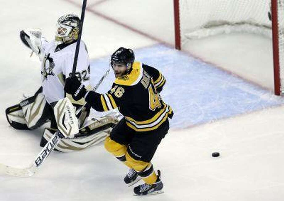 Boston Bruins center David Krejci (46) celebrates next to Pittsburgh Penguins goalie Tomas Vokoun, left, as the puck shot by Boston Bruins defenseman Adam McQuaid rattles out of the net after a goal during the third period of Game 4 in the Eastern Conference finals of the NHL hockey Stanley Cup playoffs, in Boston on Friday, June 7, 2013. (AP Photo/Charles Krupa) Photo: AP / AP