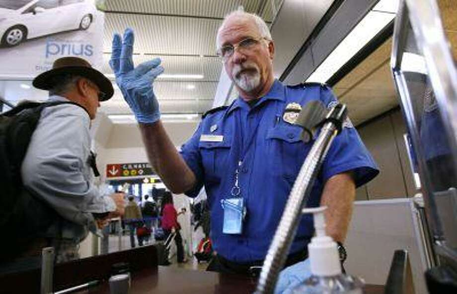 FILE - In this Jan. 4, 2010 file photo, TSA officer Robert Howard signals an airline passenger forward at a security check-point at Seattle-Tacoma International Airport in SeaTac, Wash. John Pistole, The head of the Transportation Security Administration (TSA) says he's dropping a proposal that would have let airline passengers carry small knives, souvenir bats, golf clubs and other sports equipment onto planes. The proposal had drawn fierce opposition from lawmakers, airlines and others who said it would place passengers and crews at risk. (AP Photo/Elaine Thompson, File) Photo: AP / AP