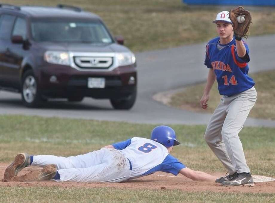 JOHN HAEGER @ONEIDAPHOTO ON TWITTER/ONEIDA DAILY DISPATCH Oneida's Drew Mallinder (14) waits on a throw as New York Mills' Zach Vennaro (8) slides safely back to first in the top of the first inning of play on Monday, April 8, 2013 in Oneida.