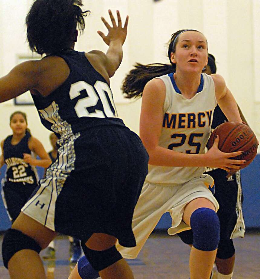 Catherine Avalone/The Middletown PressMercy sophomore forward Maura Fitzpatrick drives with her eye on the hoop as Hillhouse senior forward Jacqueline Brown defends Friday night in Middletown. The Mercy Tigers defeated the Hillhouse Academics 63-23.