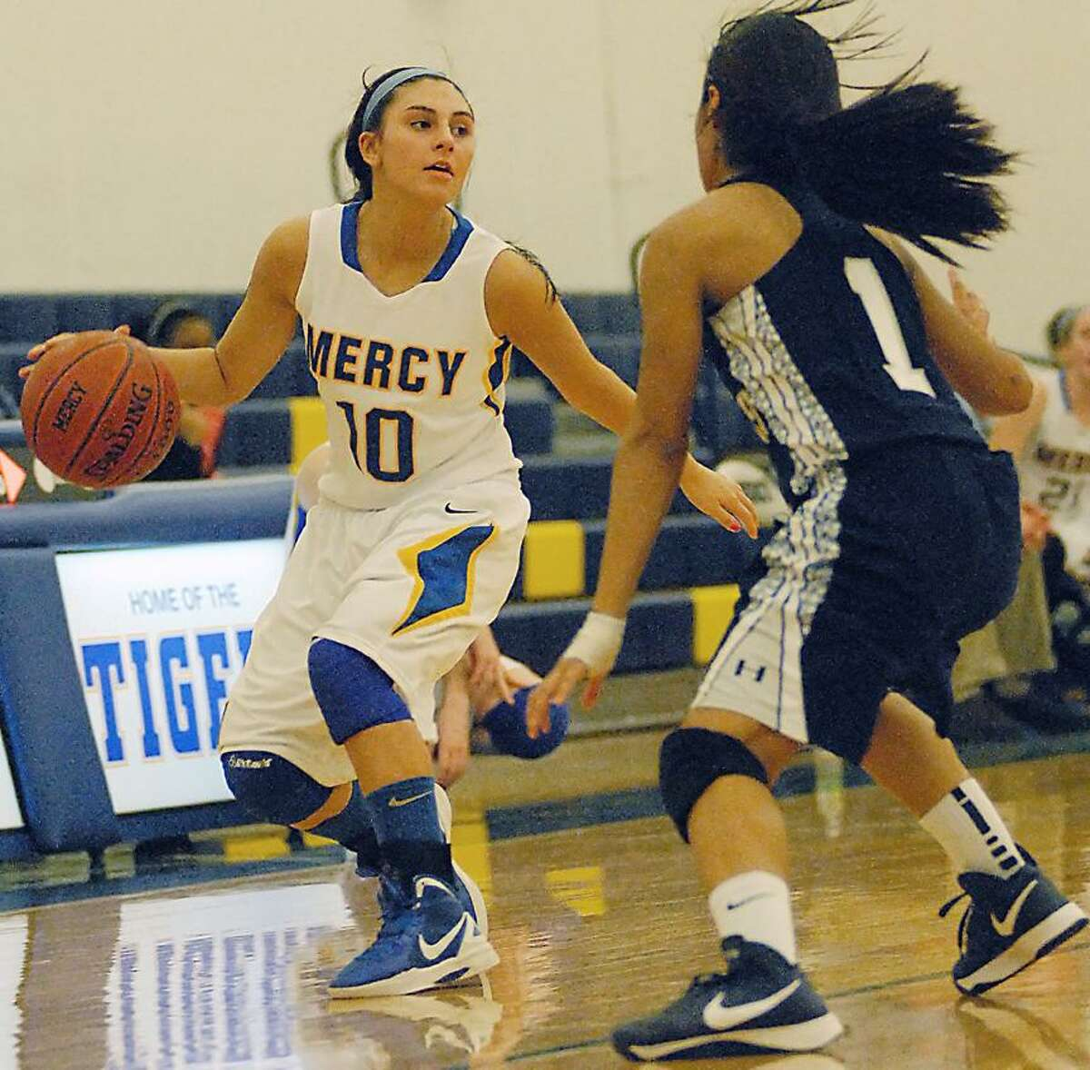 Catherine Avalone/The Middletown PressMercy senior Jordyn Nappi looks to make a pass around Hillhouse's Allegra Jones Friday night. The Mercy Tigers defeated the Hillhouse Academics 63-23.