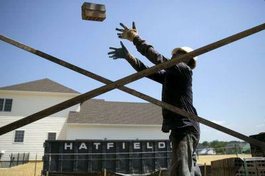A contractor tosses bricks onto scaffolding at a home under construction at the Toll Brothers Inc. Cattail Overlook development in Glenelg, Md., on May 30, 2013.