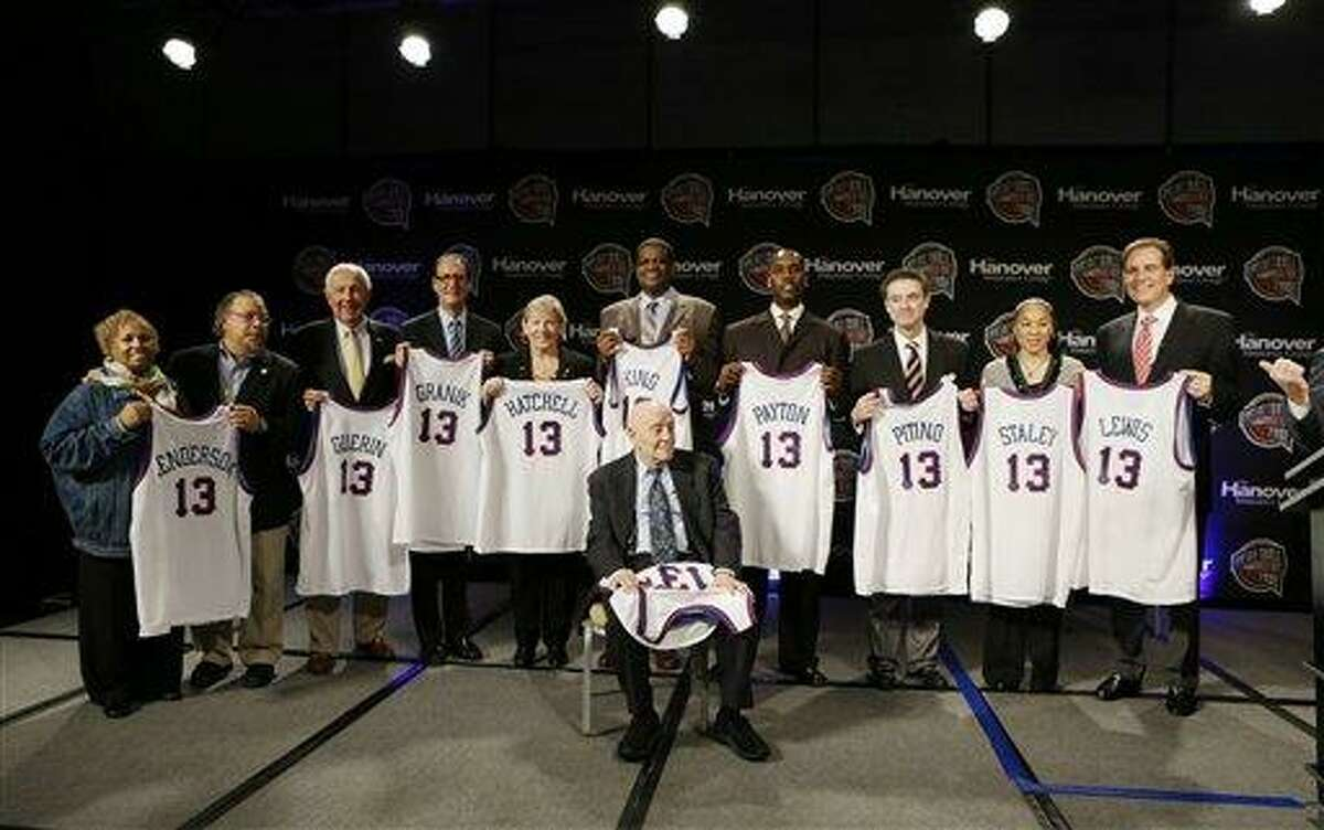 Members of the 2013 Naismith Memorial Basketball Hall of Fame class line up for a photo after inductee announcements, Monday, April 8, 2013, in Atlanta, Georgia. Shown sitting behind Jerry Tarkanian from left are Edwin and Nikki Henderson representing Dr. E.B. Henderson, Richard Guerin, Russ Granik, Sylvia Hatchell, Bernard King, Gary Payton, Rick Pitino, Dawn Staley, and CBS announcer Jim Nantz representing Guy Lewis. (AP Photo/Charlie Neibergall)