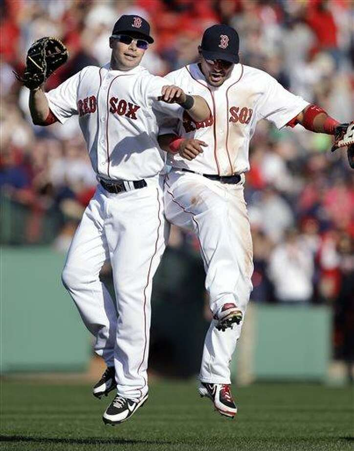 Boston Red Sox left fielder Daniel Nava, left, and right fielder Shane Victorino celebrate their 3-1 victory over the Baltimore Orioles in a baseball game at Fenway Park in Boston, Monday, April 8, 2013. (AP Photo/Elise Amendola) Photo: ASSOCIATED PRESS / AP2013