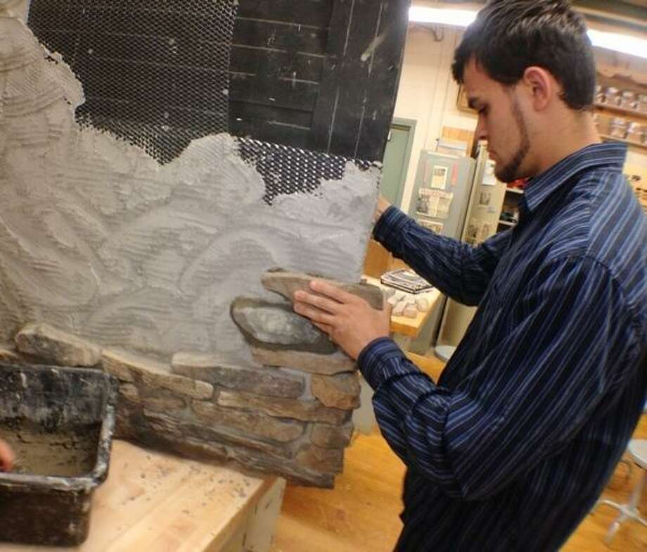 JOHN HAEGER @ONEIDAPHOTO ON TWITTER/ONEIDA DAILY DISPATCH Oneida High School student Patrick Pennise places  a piece of culture stone  on a wall during class on Tuesday, June 4, 2013 at Oneida High School.