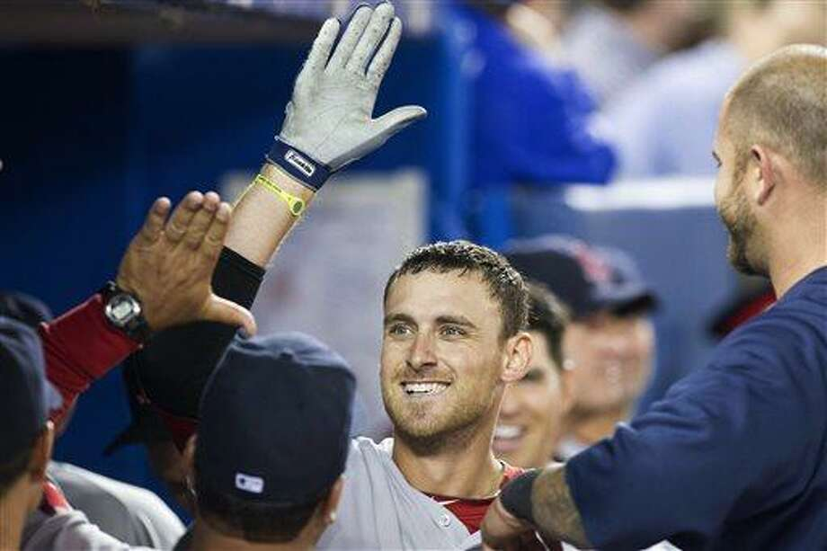 Boston Red Sox Will Middlebrooks celebrates in the dugout after hitting a home run off Toronto Blue Jays pitcher Dave Bush during seventh inning AL baseball action in Toronto on Sunday April 7, 2013. (AP PHOTO/THE CANADIAN PRESS,Chris Young) Photo: AP / CP