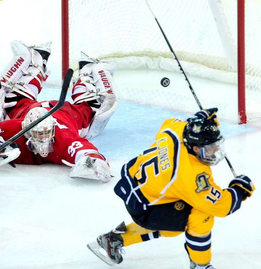 Kellen Jones (right) of Quinnipiac scores past Cornell goalie Andy Iles (left) in the second period of the ECAC quarterfinals on 3/15/2013. Photo by Arnold Gold/New Haven Register   AG0488A