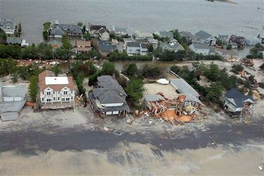 This Oct. 30, 2012 file photo provided by the U.S.Air Force shows an aerial view of  damage to the New Jersey shoreline following Superstorm Sandy. There are a rising number of homes damaged by Sandy hitting the market -  ranging from 10 percent off pre-storm prices for upscale homes in New York?s Long Island and the Jersey Shore to up to 60 percent off modest bungalows in Staten Island and Queens - but it?s very much a game of buyer beware.  (AP Photo/U.S. Air Force, Master Sgt. Mark C. Olsen, File) Photo: AP / U.S. Air Force