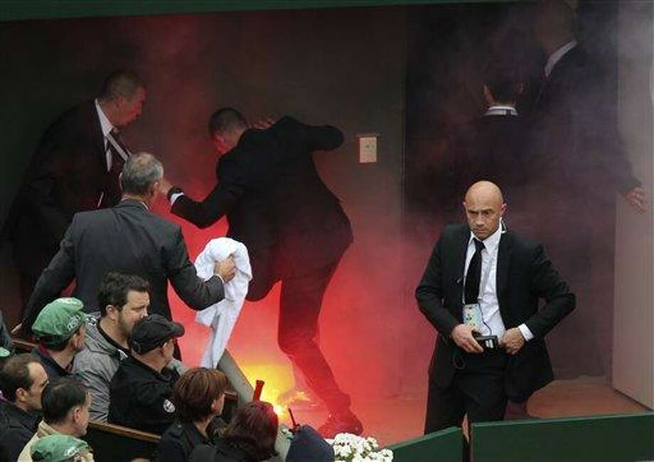 Security officer try to put out a fire after a demonstrator ran onto center court with flares as Spain's Rafael Nadal plays compatriot David Ferrer during the men's final match of the French Open tennis tournament at the Roland Garros stadium Sunday, June 9, 2013 in Paris. (AP Photo/David Vincent) Photo: AP / AP