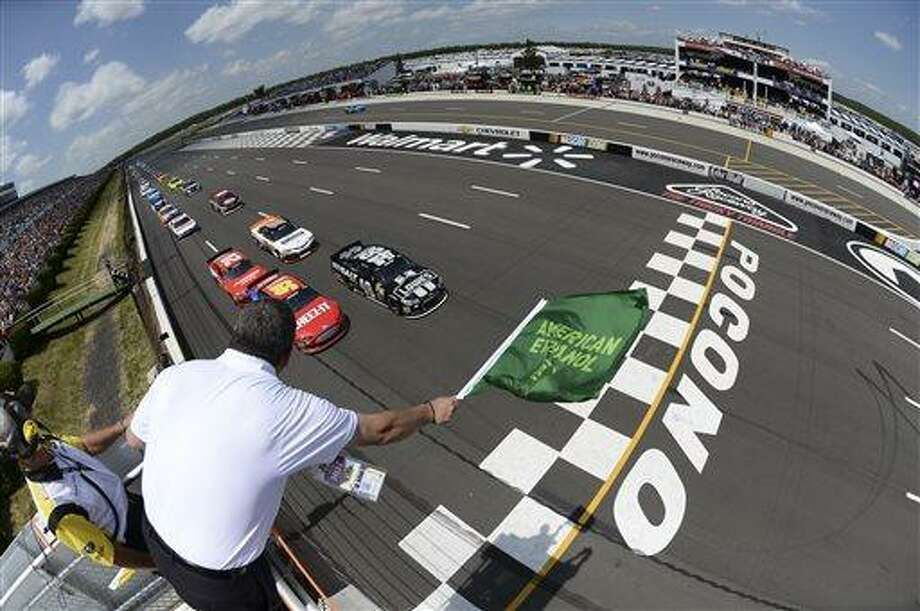 In this handout photo provided by NASCAR, Jimmie Johnson (48) and Carl Edwards (99) lead the field to the green flag to start the NASCAR Pocono 400 auto race, June 9, 2013 in Long Pond, Pa. (AP Photo/NASCAR, Patrick Smith) Photo: AP / NASCAR