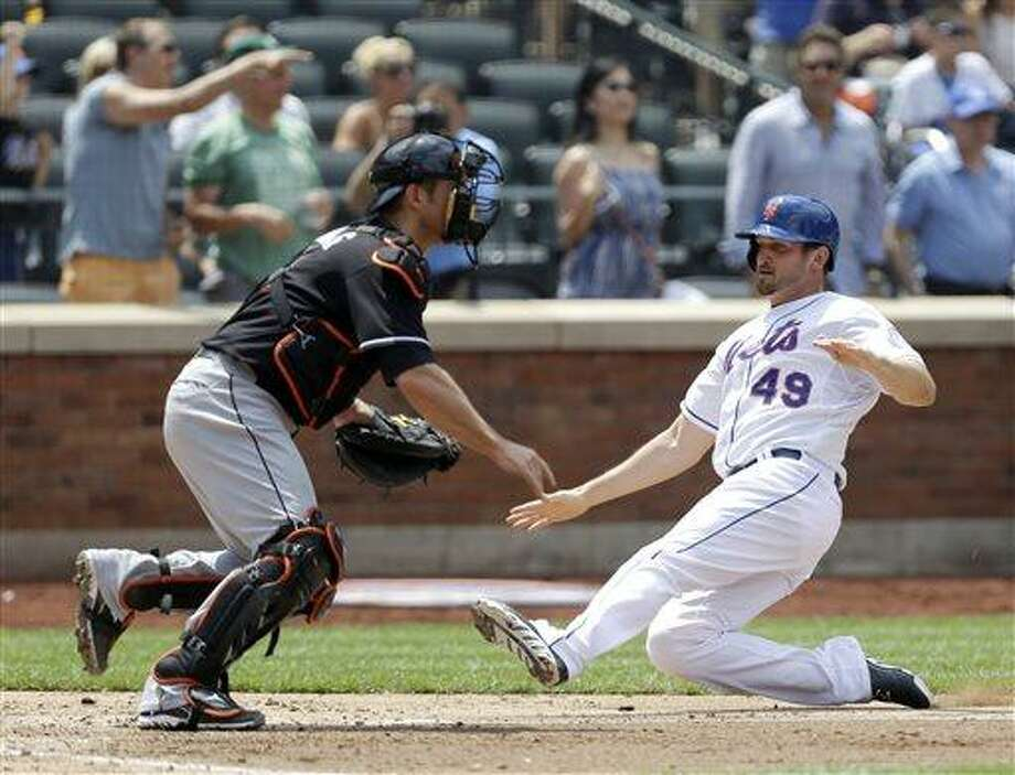 New York Mets' Jonathon Niese (49) slides in to score ahead of the throw to Miami Marlins catcher Jeff Mathis on David Wright's two-run double in the third inning of a baseball game in New York, Sunday, June 9, 2013. (AP Photo/Kathy Willens) Photo: AP / AP