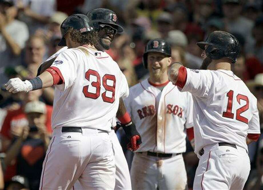 Boston Red Sox designated hitter David Ortiz congratulates teammate Jarrod Saltalamacchia (39) after he hit a three-run home run scoring him and Mike Napolis (12) during the seventh inning of a baseball game against the Los Angeles Angels, Sunday, June 9, 2013 at Fenway Park in Boston. (AP Photo/Mary Schwalm) Photo: AP / FR158029 AP