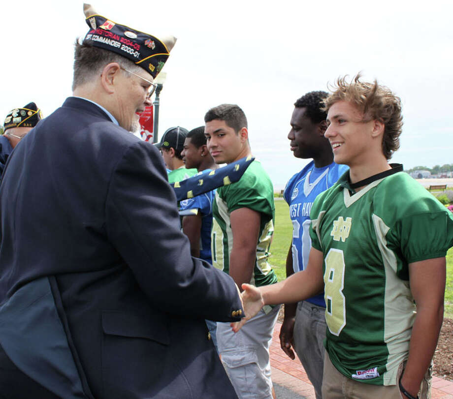 Veteran Frazier Brinley from Westbrook shaking hands with West Haven football player Provitz Edward.  Nicole Dellolio/For the Register